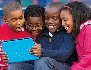 four kids using a tablet